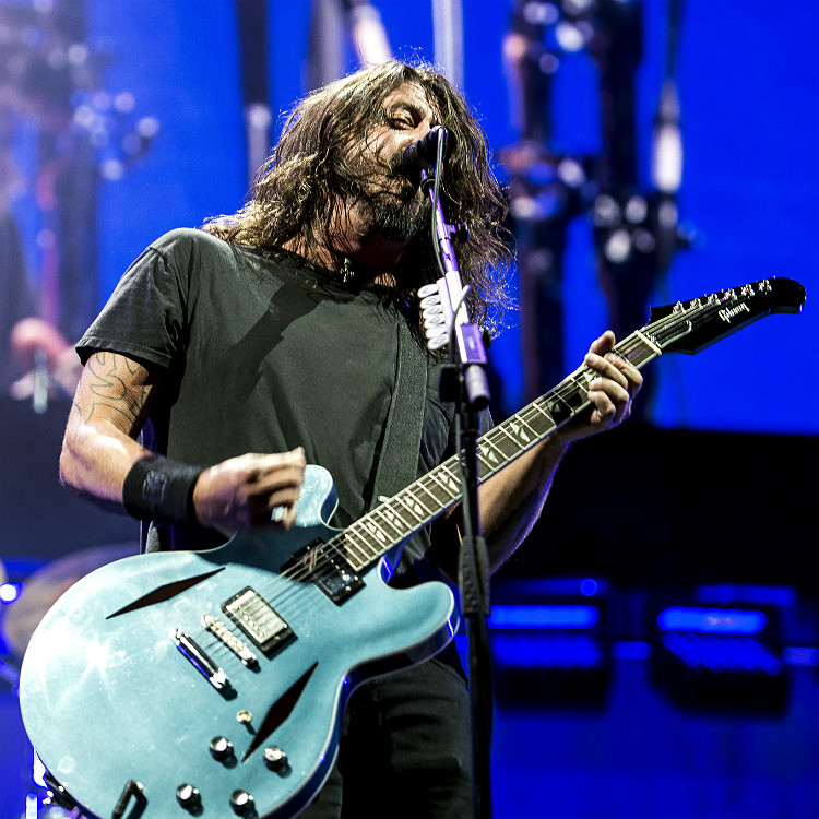 Foo Fighters frontman Dave Grohl gives his shoe to a fan on crutches